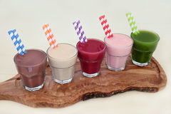 Health Food Supplement Drinks. Of chocolate whey protein, maca root herb, acai berry, pomegranate fruit and wheat grass on an olive wood board. Also used by stock photos