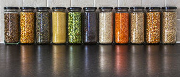 Health Food - variety of herbs, seeds and pulses in spice jars. Royalty Free Stock Image