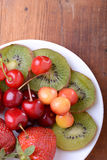 Health fruit with cherry, strawberry, kiwi on wooden plate Royalty Free Stock Photography