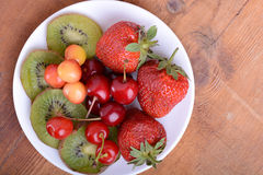 Health fruit with cherry, strawberry, kiwi on wooden plate Royalty Free Stock Images