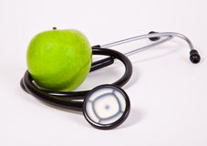 Health and fruits. Stethoscope and a green  apple on a white Background Royalty Free Stock Image