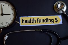 Online Doctor on the print paper with Healthcare Concept Inspiration. alarm clock, Black stethoscope.Health Funding $ on the print. Health Funding $ on the print royalty free stock photos