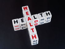 Health goes with wealth. Text ' health ' and ' wealth ' inscribed on small white cubes in uppercase letters and arranged crossword style with common letter ' a Royalty Free Stock Image
