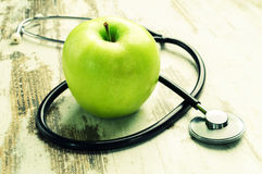 Health. Green apple with medical stethoscope Royalty Free Stock Photos