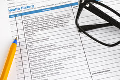 Health History form with glasses and pen. Stock Photography