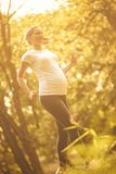 Health is important for both. Pregnant woman jogging and exercise trough park. Close up. Copy space royalty free stock images