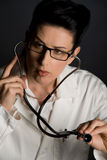 Health Inspection. Close-up of female doctor listening during medical exam Royalty Free Stock Photography