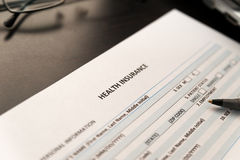 Health insurance application form on a wooden table Stock Images