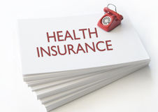 Health insurance business card. Small telephone on top of a stack of business cards with health insurance Stock Photography
