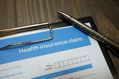 Health insurance claim form with pen on desk. Health insurance claim form with pen on wooden desk stock image