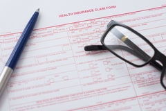 Health insurance claim form with pen and glasses Royalty Free Stock Images