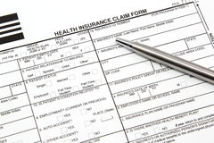 Health Insurance Claim Form with Silver Pen. A health insurance claim form with a silver pen ready to be filled out for manual submission to an insurance carrier stock image