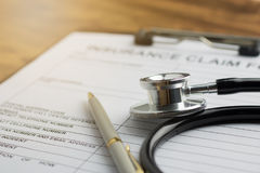 Health insurance claim. Form with stethoscope on wood table selective focus Stock Photos