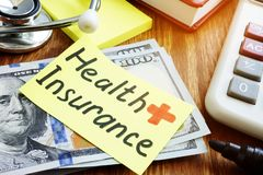 Health Insurance concept. Cash and stethoscope with calculator stock image