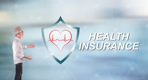 A health insurance concept explained by a businessman on a wall screen. Businessman showing a health insurance concept on a wall screen royalty free stock image