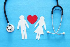 Health Insurance . concept image of Stethoscope and family on wooden table. top view. Health Insurance . concept image of Stethoscope and couple on wooden table royalty free stock photos