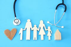 Health Insurance . concept image of Stethoscope and family on wooden table. top view. Health Insurance . concept image of Stethoscope and family on wooden table royalty free stock photo