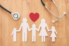 Health Insurance . concept image of Stethoscope and family on wooden table. Top view stock image