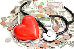 Health insurance concept with red heart, pills and medical instruments on money pile Royalty Free Stock Images