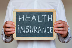 Health insurance. Concept, text on chalkboard in hands of doctor Royalty Free Stock Photography