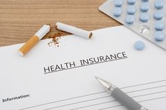 Health insurance document with pills and broken cigarette Royalty Free Stock Images