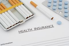 Health insurance document with pills and cigarettes Stock Images