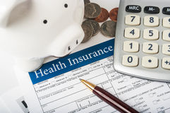 Health insurance form with piggy bank. Calculator and coins Royalty Free Stock Photography