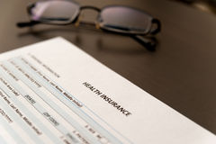 Health insurance form on a table with glasses Royalty Free Stock Images