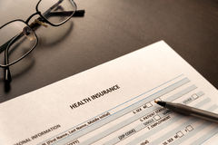 Health insurance form on a table with glasses and pen Royalty Free Stock Photo