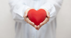 Health insurance or love concept. Small red heart in man's hands Stock Photo