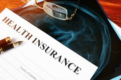 Health insurance policy concept. Claim form on a table. Stock Photos