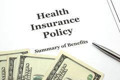 Health Insurance Policy with Pen and Cash. A health insurance policy with a pen ready for signing surround by cash in hundred dollar bills Royalty Free Stock Photo