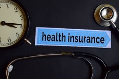 Health Insurance on the print paper with Healthcare Concept Inspiration. alarm clock, Black stethoscope. royalty free stock photography