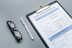 Health insurance for reception at the doctor. Document, pen, glasseson dark grey background Stock Photos
