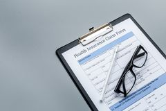 Health insurance for reception at the doctor. Document, pen, glasseson dark grey background copyspace Royalty Free Stock Photography