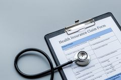 Health insurance for reception at the doctor. Document and stethoscope on dark grey background copyspace Royalty Free Stock Images