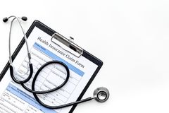 Health insurance for reception at the doctor. Document, stethoscope, pad, glasses on white background top view copyspace Stock Images