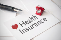 Health insurance. Small telephone on top of business card with health insurance Stock Images