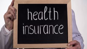 Health insurance text on blackboard in doctor hands, expensive family medicine. Stock footage royalty free stock photo