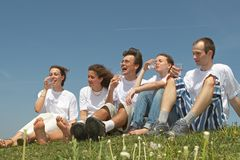 Health life. Five nice young people in white vests sit on a grass and drink water from plastic glasses Stock Photos