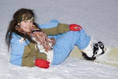 Health lifestyle image of teens snowboarder girl. A health lifestyle image of young adult (age 18-20) snowboarder girl after incidence  in the evening mountains Royalty Free Stock Photography
