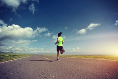 Lifestyle woman trail runner running on country road Stock Image