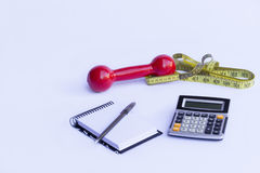 Health measures. Dumbbell notepad calculator and tape measure. White background Stock Image