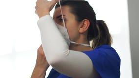 Female doctor or nurse wearing respirator mask