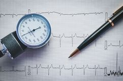 Health monitoring with tonometer and cardiogram. Medical blood pressure manometer and black pen lying on cardiogram ECG royalty free stock images