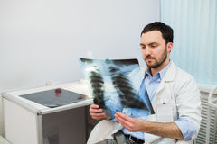 Health and mood. Serious Doctor talking to patient keeps chest X-ray in hands while sitting at a table the hospital. Health and mood. Serious Doctor talking to Stock Photos
