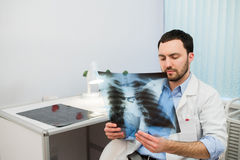 Health and mood. Serious Doctor talking to patient keeps chest X-ray in hands while sitting at a table the hospital. Health and mood. Serious Doctor talking to Stock Photography