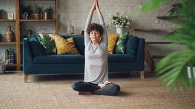 Health-oriented young woman is stretching her arms and body then resting in lotus position with hands on knees sitting. On floor at home. Millennials, well stock footage