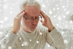 Senior man suffering from headache at home. Health, pain, stress and people concept - senior man suffering from headache at home over snow Royalty Free Stock Image