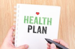 Health plan word on white ring binder notebook with hand holding Royalty Free Stock Image